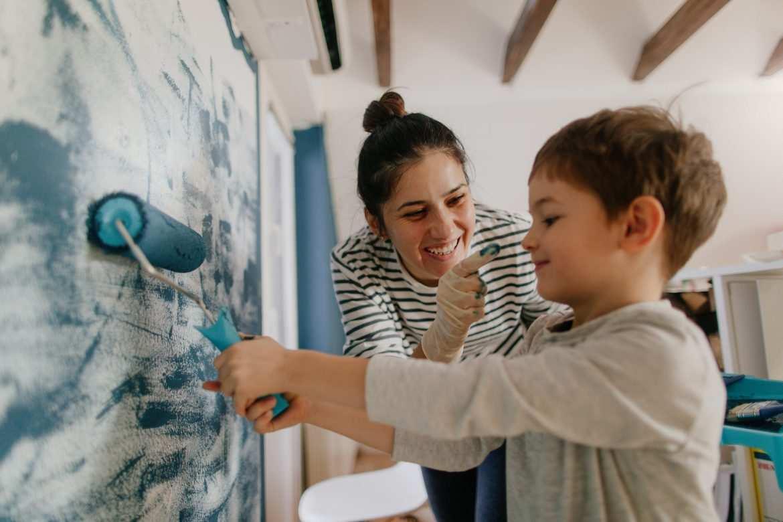 Une mère et son fils en train de peindre un mur