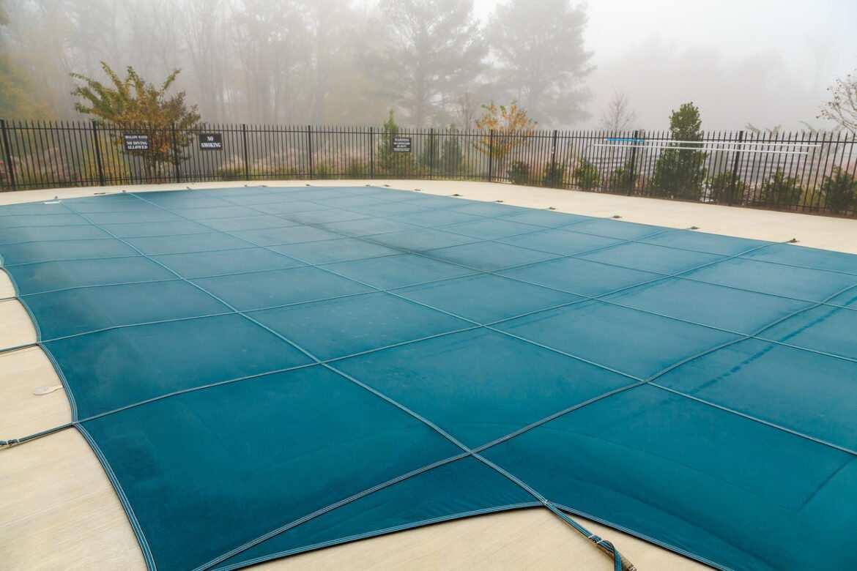Une piscine recouverte d'une bâche pendant l'hiver