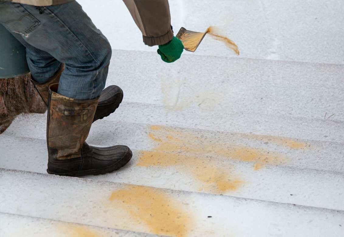 Un homme parsème du sable sur ses escaliers enneigés