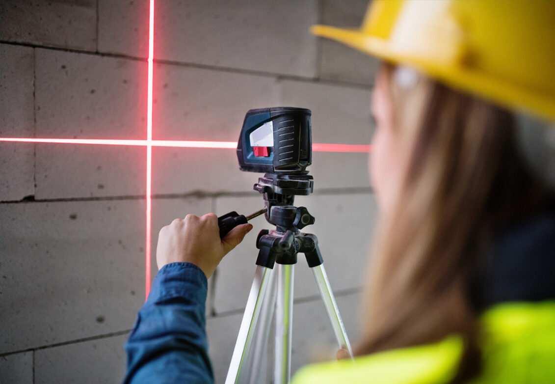 Une femme utilise un niveau laser sur un chantier