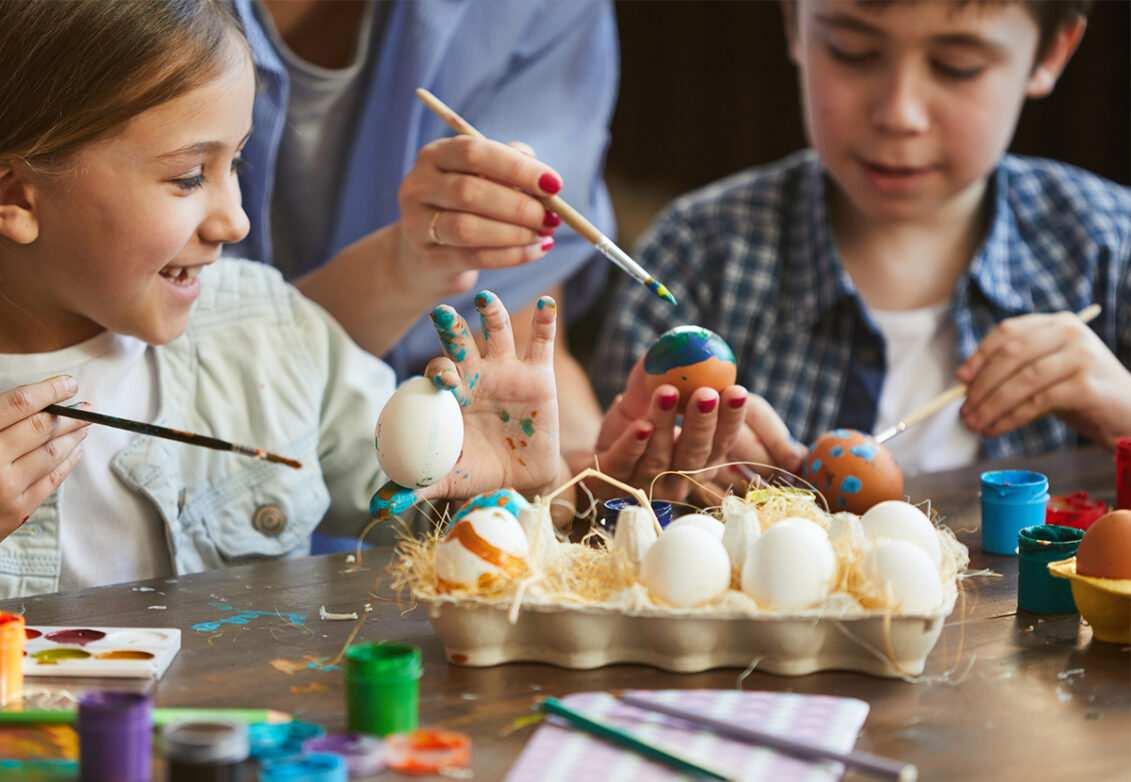 Des enfants en train de décorer des œufs de Pâques