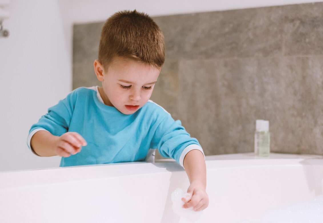 Un petit garçon qui joue avec la mousse de sa baignoire