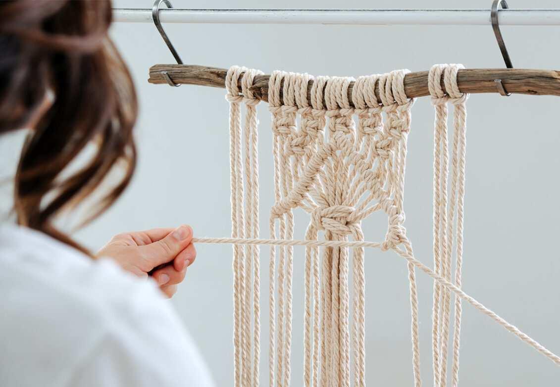Une femme en train de fabriquer une décoration en macramé