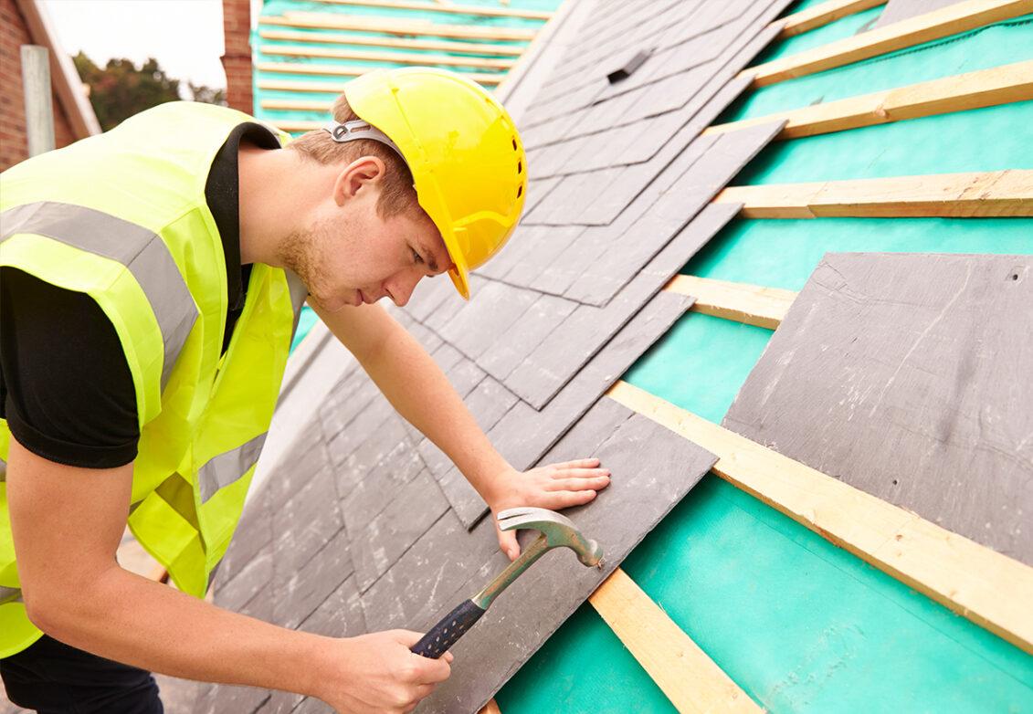 Un homme en tenue de chantier qui installe une toiture en ardoise