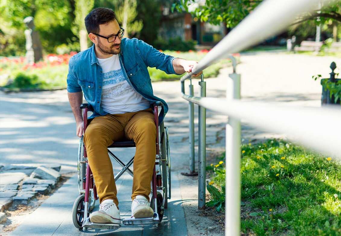 Une personne à mobilité réduite s'aide d'une rampe pour monter