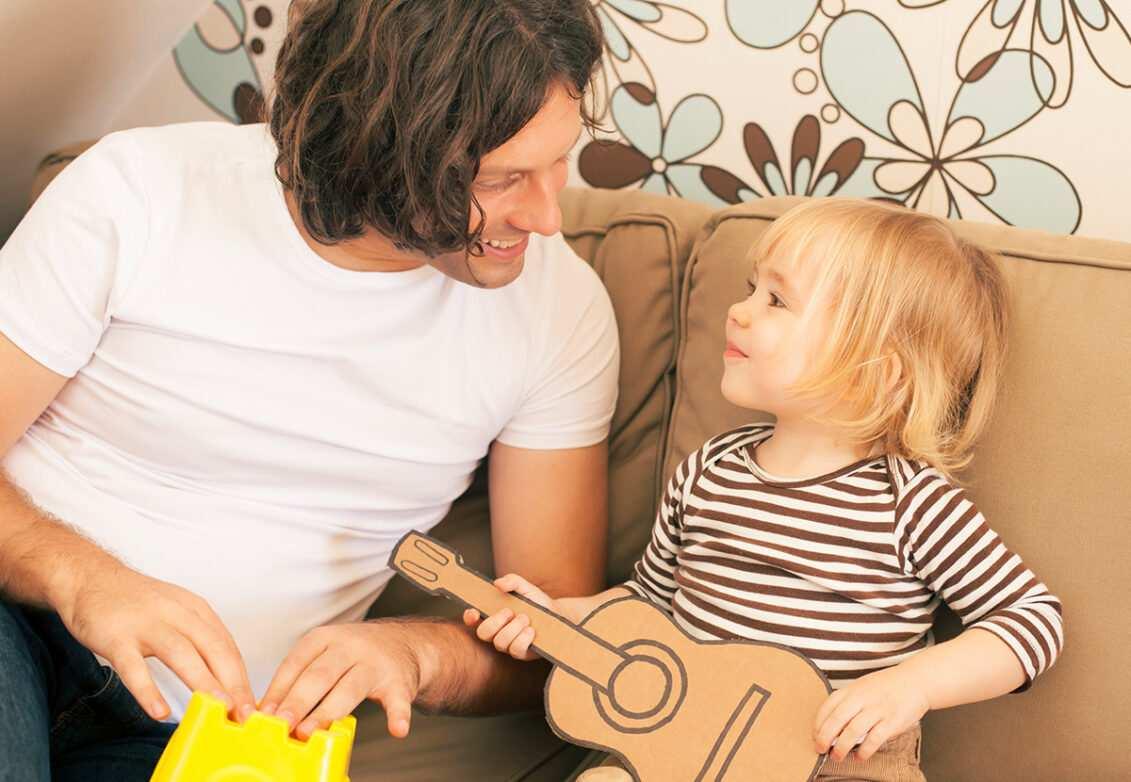 Un père et sa fille avec une guitare en carton