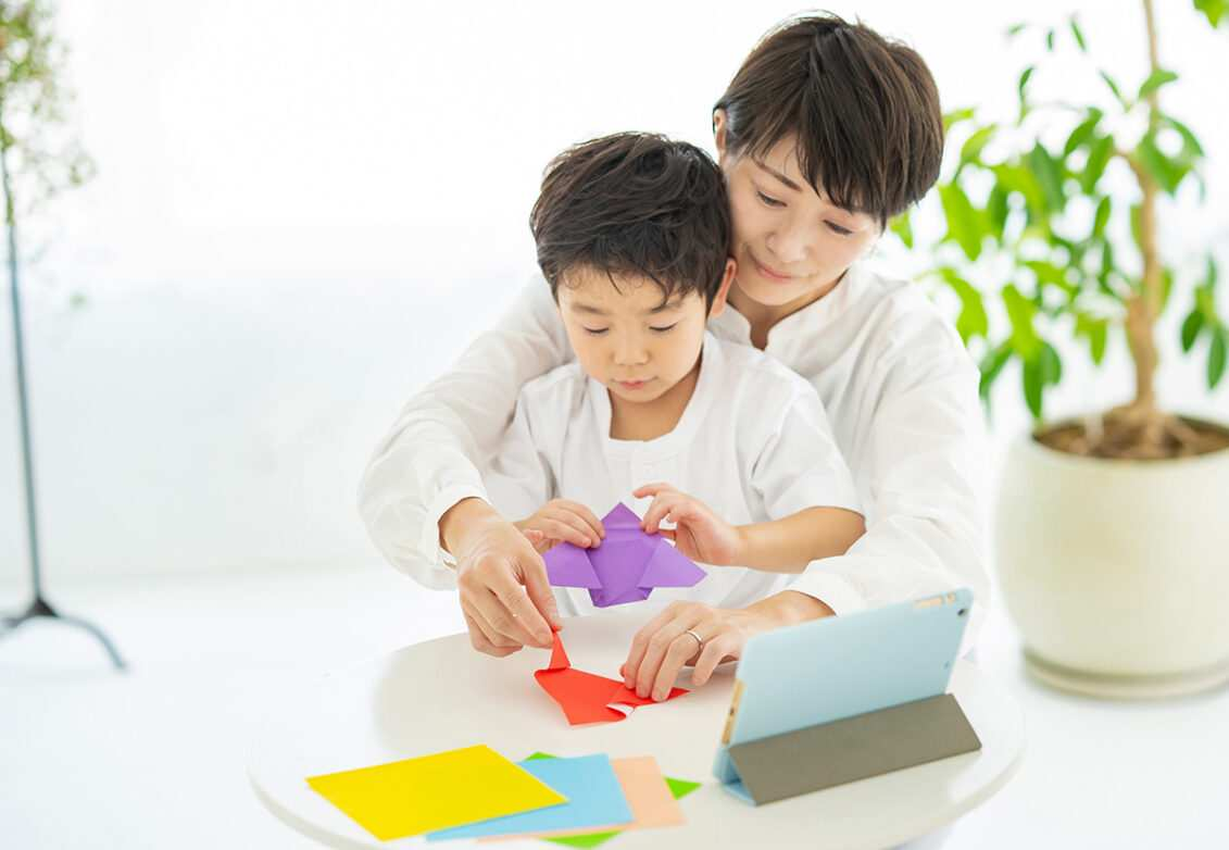 Une femme et son fils en train de fabriquer des origamis