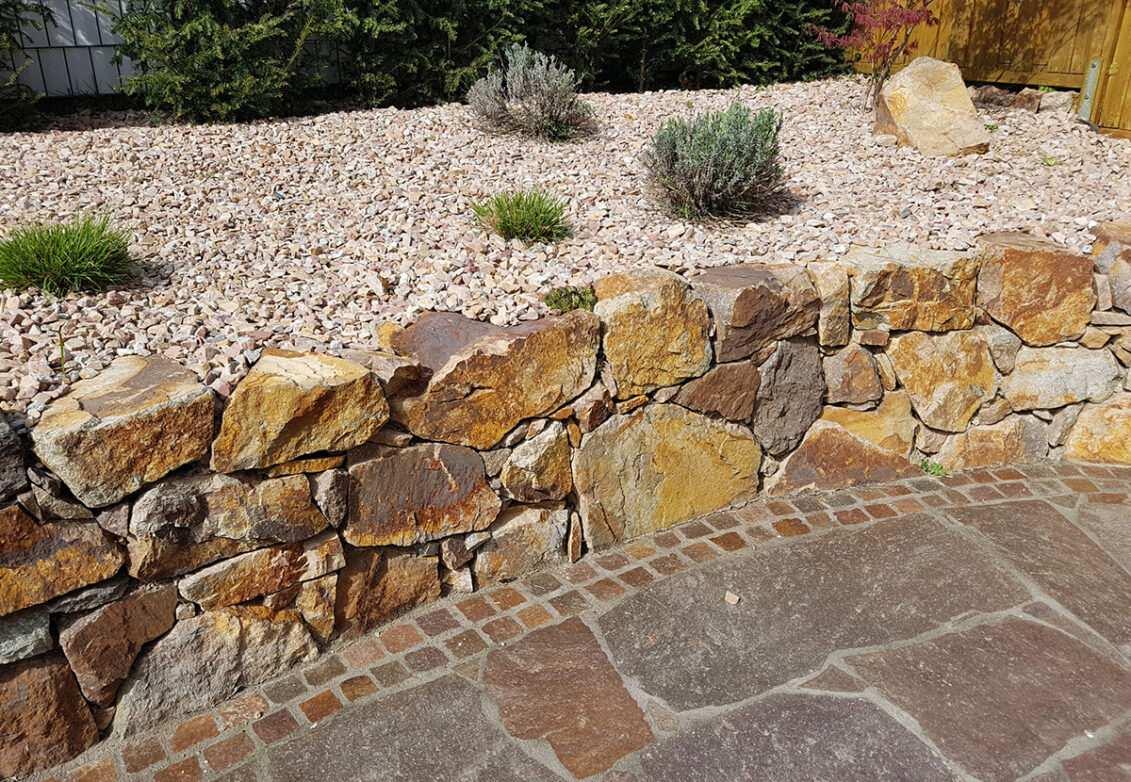 un mur en pierres sèches dans un jardin