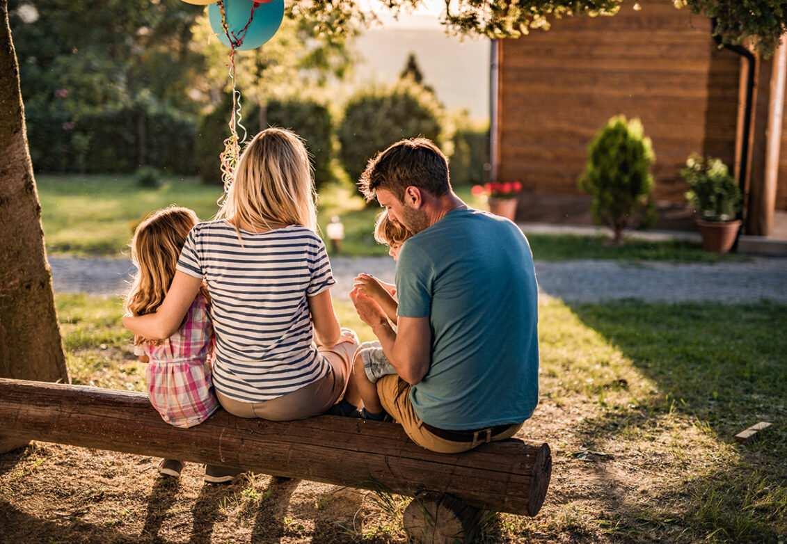 Une famille assise sur un banc en rondin de bois dans le jardin