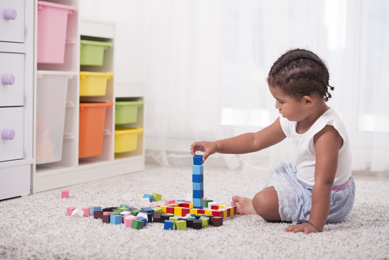 Un enfant joue sur sa moquette